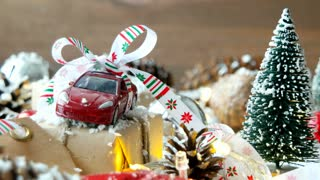christmas-and-new-year-background-with-toy-car-present-with-ribbon-balls-pinecones-and-different-decorations-on-snow_sel5vrfwx_thumbnail-small01.jpg